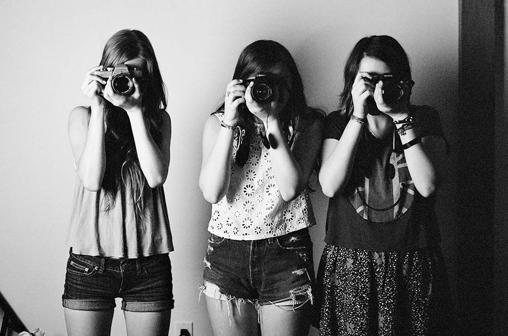 Students in the summer teen program posing and holding their cameras